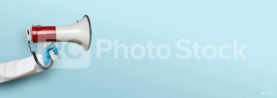 hand of medic or Nurse with gloves and a megaphone in front of an empty blue background, banner size, with copyspace for your individual text.  : Stock Photo or Stock Video Download rcfotostock photos, images and assets rcfotostock | RC-Photo-Stock.: