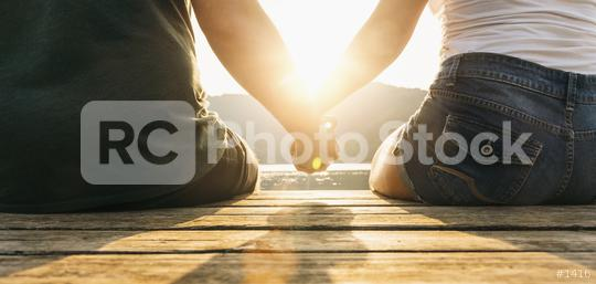 Happy moments together. Happy young couple holding hands sitting on the pier at a lake on sunset  : Stock Photo or Stock Video Download rcfotostock photos, images and assets rcfotostock | RC-Photo-Stock.:
