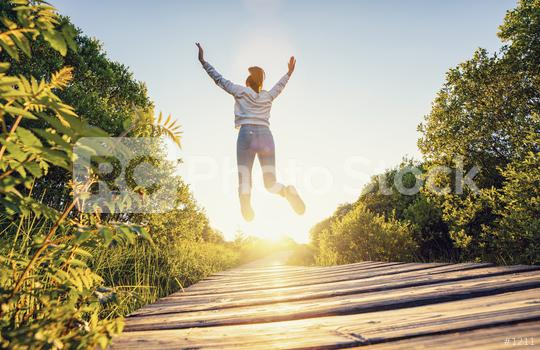 Happy woman jumping with raised hands and legs, and enjoying life over a Wooden path at sunset  : Stock Photo or Stock Video Download rcfotostock photos, images and assets rcfotostock | RC-Photo-Stock.: