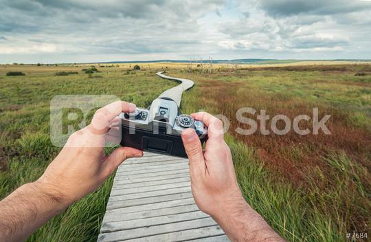 male hand holding a vintage camera against the a landscape with boardwalk to take a picture, pov, point of view perspective.  : Stock Photo or Stock Video Download rcfotostock photos, images and assets rcfotostock | RC-Photo-Stock.: