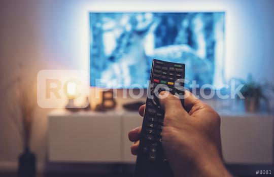 man Watching movie and using remote control  : Stock Photo or Stock Video Download rcfotostock photos, images and assets rcfotostock | RC-Photo-Stock.: