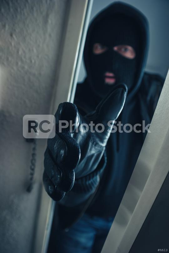 masked burglar entering a victim