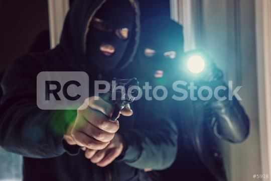 masked burglar with gun breaking and entering into a victim
