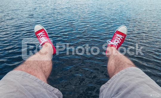 Mens legs in sneakers in background of a sea landscape Summer Beach Relaxing Concept, Point of view shot  : Stock Photo or Stock Video Download rcfotostock photos, images and assets rcfotostock | RC-Photo-Stock.:
