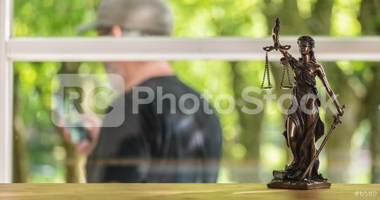 Statue of Justice - lady justice or Iustitia / Justitia the Roman goddess of Justice in a lawyer office with a man using a smartphone  : Stock Photo or Stock Video Download rcfotostock photos, images and assets rcfotostock | RC-Photo-Stock.: