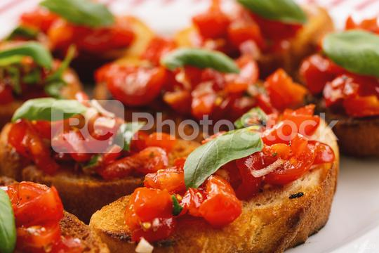 Tasty savory tomato Italian appetizers, or bruschetta, on slices of toasted baguette garnished with basil, close up  : Stock Photo or Stock Video Download rcfotostock photos, images and assets rcfotostock | RC-Photo-Stock.: