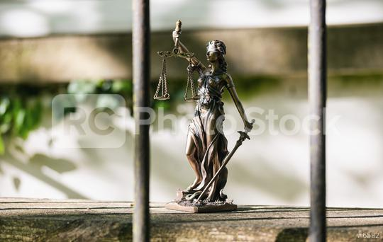 The Statue of Justice - lady justice or Iustitia / Justitia the Roman goddess of Justice against a jail grid  : Stock Photo or Stock Video Download rcfotostock photos, images and assets rcfotostock | RC-Photo-Stock.: