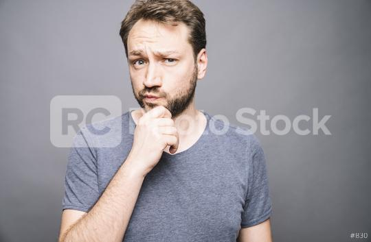thoughtful man who looks away touching his chin and weighs the pluses and minuses of the offer  : Stock Photo or Stock Video Download rcfotostock photos, images and assets rcfotostock | RC-Photo-Stock.:
