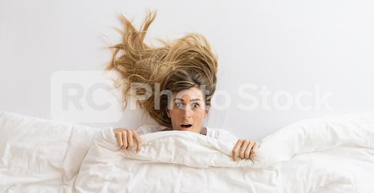 Top view of a beautiful woman that is surprise and looking at camera while lying in bed under blanket  : Stock Photo or Stock Video Download rcfotostock photos, images and assets rcfotostock | RC-Photo-Stock.: