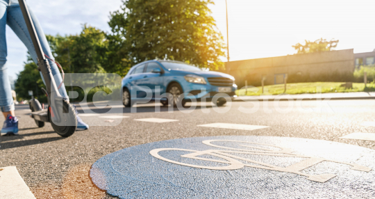 view of a electric kick scooter or e-scooter at a Bicycle road sign with car passing on a summer day, accident concept image  : Stock Photo or Stock Video Download rcfotostock photos, images and assets rcfotostock | RC-Photo-Stock.: