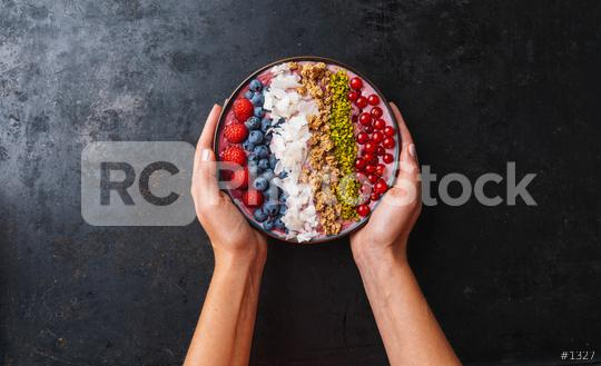 Woman hands hold a Healthy breakfast bowl, wirh blueberry smoothie with, raspberry, blueberrys, coconut, nuts and currants toppings  : Stock Photo or Stock Video Download rcfotostock photos, images and assets rcfotostock | RC-Photo-Stock.:
