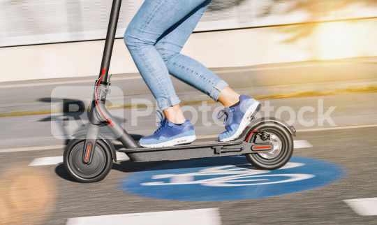 woman riding electric kick scooter or e-scooter over a Bicycle road sign at cityscape, motion blur  : Stock Photo or Stock Video Download rcfotostock photos, images and assets rcfotostock | RC-Photo-Stock.: