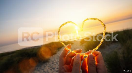 womand holding Heart shape made of led lights on the beach near the sea,  copyspace for your individual text.  : Stock Photo or Stock Video Download rcfotostock photos, images and assets rcfotostock | RC-Photo-Stock.: