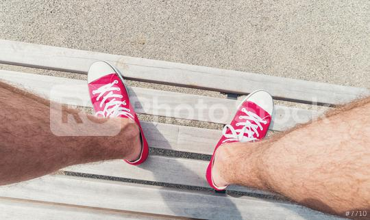 Young man in Red Sneakers sits on a bench at a summer day, Point of view shot  : Stock Photo or Stock Video Download rcfotostock photos, images and assets rcfotostock | RC-Photo-Stock.: