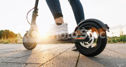Young woman is ready to discover the urban city at sunset with electric scooter or e-scooter, Electric urban transportation concept image  : Stock Photo or Stock Video Download rcfotostock photos, images and assets rcfotostock | RC-Photo-Stock.: