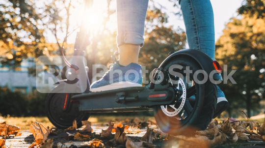 young woman on the electric scooter on the road in autumn at sunset  : Stock Photo or Stock Video Download rcfotostock photos, images and assets rcfotostock | RC-Photo-Stock.: